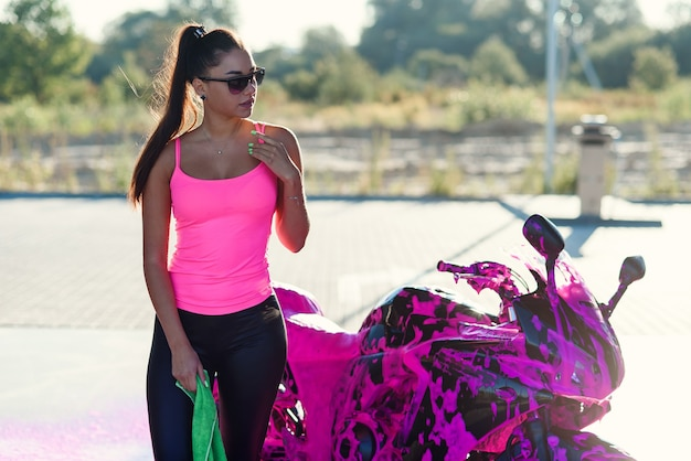 Seductive young woman in pink t-shirt poses near sport motorcycle at self service car wash in the