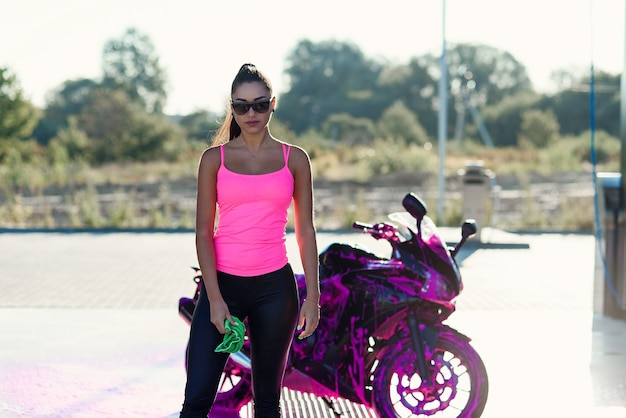 Seductive young woman in pink tshirt poses near sport motorcycle at self service car wash in the