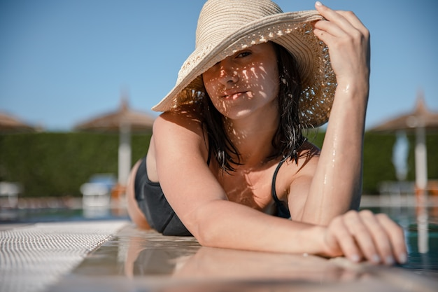 화창한 날에 밀짚 모자를 쓰고 수영장 근처 햇볕에 편안한 매혹적인 젊은 여자. 리조트 및 여름 개념.