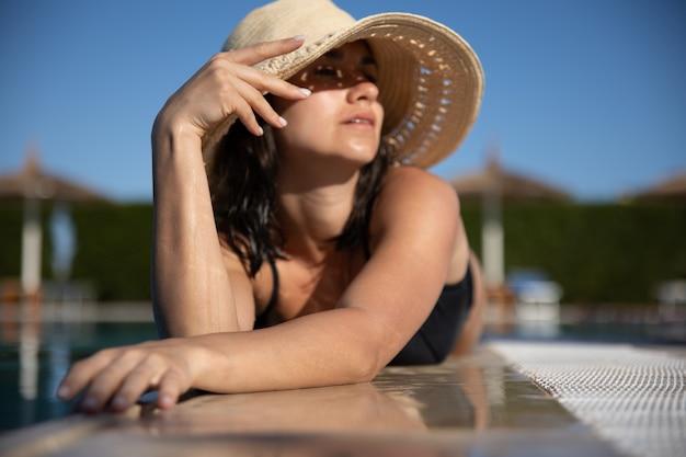 Giovane donna seducente che si distende al sole vicino alla piscina che indossa un cappello di paglia in una giornata di sole. resort e concetto estivo.