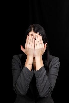 邪悪な概念を見ないでください。手で目を覆っている若い怖い女性の肖像画