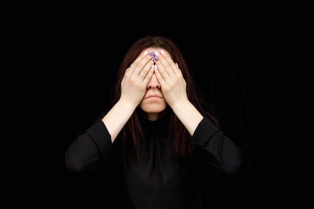 See no evil concept. portrait of a young scared woman covering eyes with hands, standing on dark studio. mixed girl close the eyes with palms while ignoring something.
