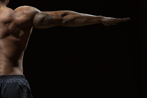 強さを見てください。腕を横に広げたコピースペースを持つ男性モデルの筋肉質の背中のクロップドショット