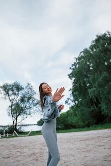 До скорого. позитивная женщина в спортивной одежде, наслаждаясь природой на пляже