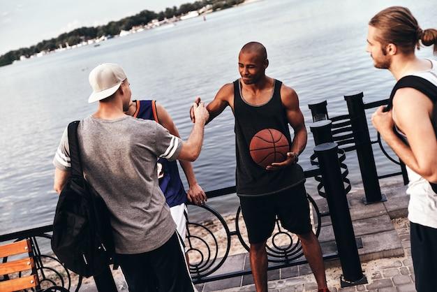 また近いうちにお会いしましょう。屋外の友人の間に立っている間握手スポーツ服を着た2人の若い男性