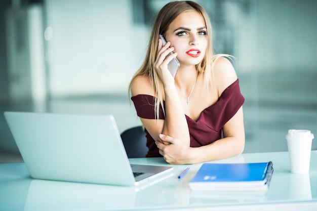 また明日ね。電話で話していると彼女の職場に座っている笑顔でラップトップを使用してガラスの陽気な若い美しい女性
