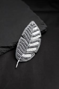 Брошь вышитая бисером в виде пера на черном фоне