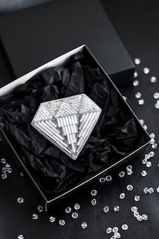 Seed beads embroidered brooch in a shape of diamond in black gift box on black surface