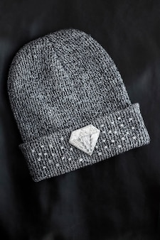 Seed beads embroidered brooch in a shape of diamond on knitted hat on black surface