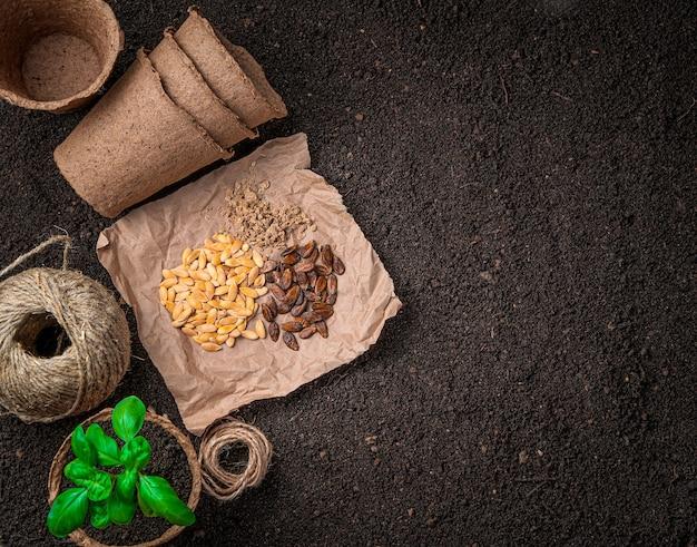 種、鍋の中のバジル、空の泥炭鉢が地面に横たわっています。コピースペースのある上面図。
