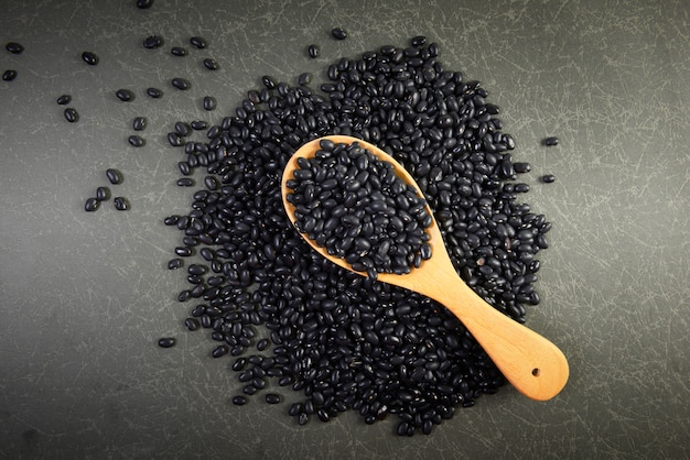 Seeds black beans useful for health in wood spoons on grey background.