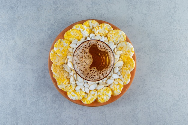 Seeds, chips and pint on the plate, on the marble surface.