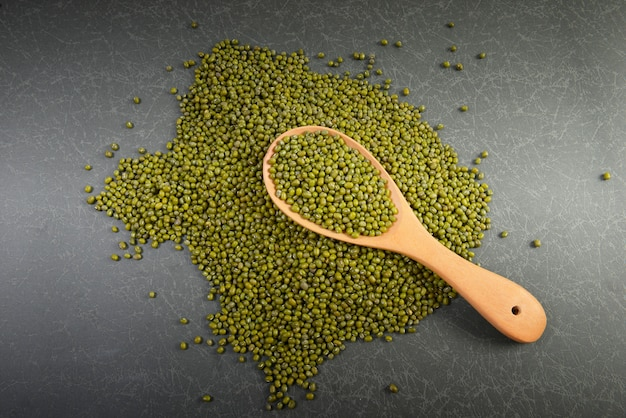 Seeds mung beans useful for health in wood spoons on grey background.