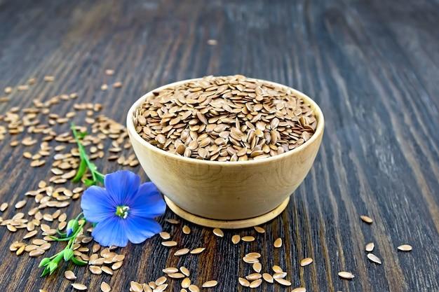 ボウルに茶色のリネンの種子、木の板の背景に青い亜麻の花