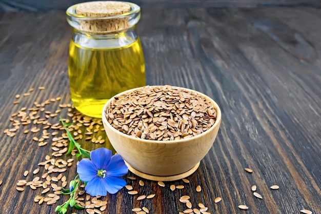 ボウルにリネンブラウンの種子、ガラスの瓶に亜麻仁油、木の板の背景に花