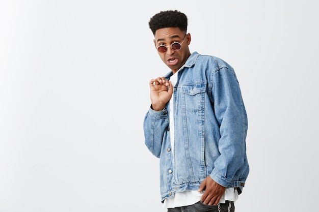 Seeing ex girlfriend with ugly guy. portrait of young attractive black-skinned man with afro haircut in white shirt, denim jacket and tan glasses looking in camera with disgust expression.