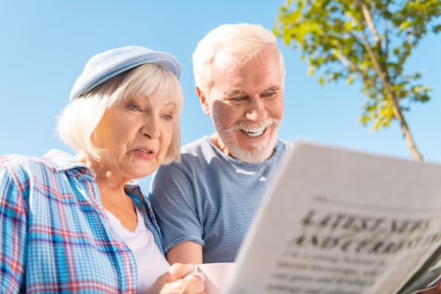Seeing story. grandmother and grandfather feeling happy seeing story about their grandchildren in newspaper