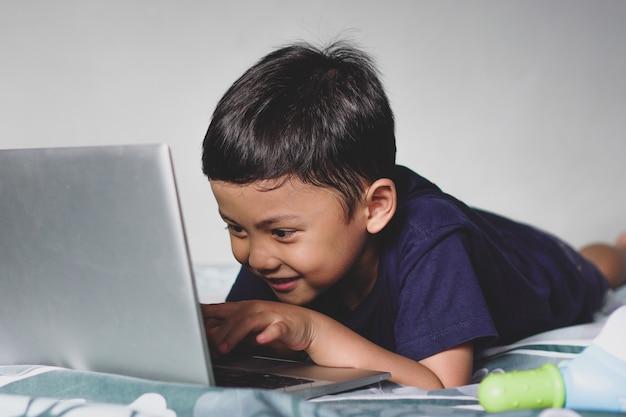 興奮した表情でベッドに横になっているアジアの少年を見て、ラップトップを使用して幸せ