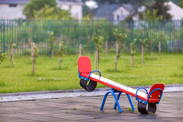 Seesaw swing in big yard with soft rubber flooring on sunny summer day.