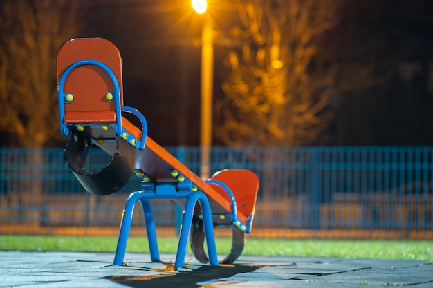 Seesaw swing in preschool yard with soft rubber flooring at night.