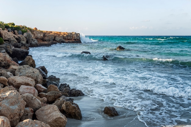 Seething blue sea with foamy waves on a rocky shore. wild beach, beautiful nature.