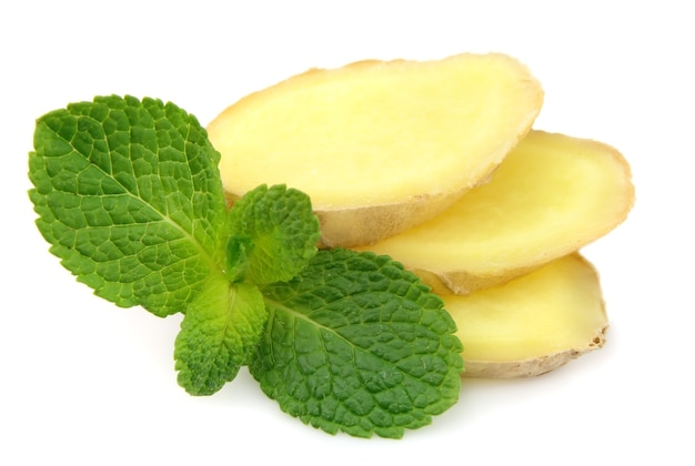 Segments of ginger root with mint on a white background