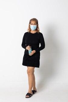 Модель женщины seinor азиатская нося положение защитной маски изолированное на белой предпосылке.