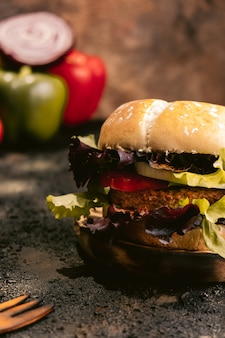 Бургер seitan vegan на деревянной поверхности с овощами. здоровая веганская еда