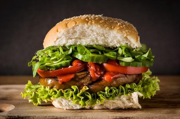 Вегетарианский бургер с seitan и овощами на деревянном столе поддельное мясо.