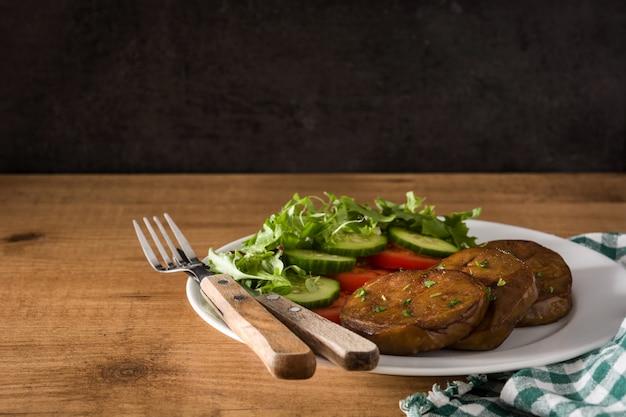 Seitan с овощами на деревянном столе копирует космос. поддельное мясо