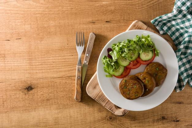 Seitan с овощами на взгляд сверху деревянного стола. копировать пространство поддельное мясо