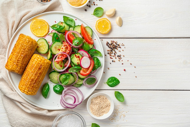 トマト、きゅうり、大根、ゴマとスパイスで味付けしたセラット、コピーするスペースのある明るい壁の平らな白いプレートに揚げたトウモロコシ。ダイエット、健康食品。
