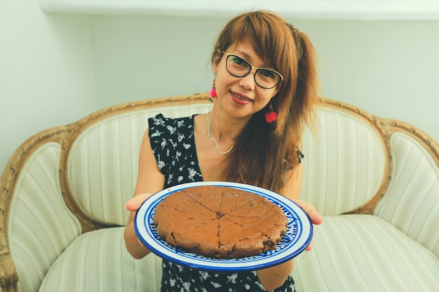 Selecitve focus on chocolate cake, beautiful young asian woman holding a plate with chocolate cake