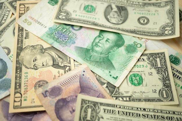 Select focus of 10 us dollar stack under china yuan banknote.