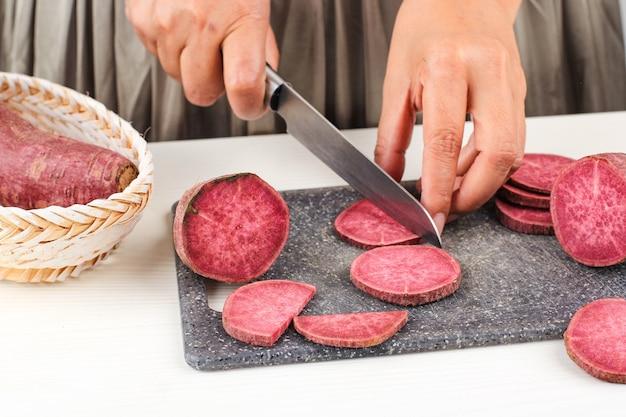 선택한 초점 여자 슬라이스 부엌에서 칼로 일본 보라색 고구마를 잘라, 흰색 배경, 주방 프로세스 개념