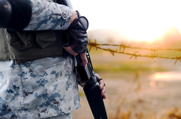 Selected focus army with rifle gun with blurred background wire fence