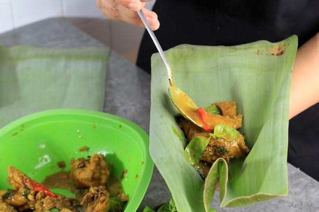 Selected focus азиатская женщина готовит пепес аям или курицу со специями, завернутую в банановый лист. обертывание курицы банановым листом и паром