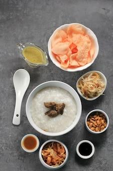 선택된 focus bubur ayam 또는 갈가리 찢긴 닭고기를 곁들인 인도네시아 쌀 죽. kerukpuk (크래커), 간장, 튀긴 콩, 삼발과 함께 제공