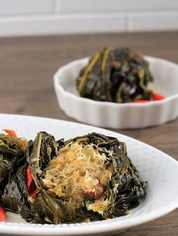 Selected focus buntil - это традиционная индонезийская еда, приготовленная из листьев папайи / маниока, фаршированных тертым кокосом, петай циной и анчоусами. популярно в яванской и суданской кухне