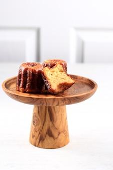 Выбранный фокус canele classic french pastry bordeaux на деревянной подставке для торта, концепция пекарни на белом фоне, копией пространства для текста