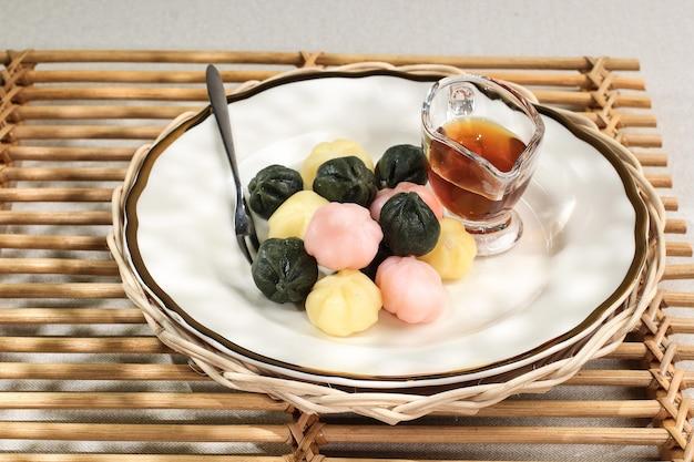 Selected focus красочный сонгпён ккультток (рисовый пирог с медовой начинкой) в деревянной тарелке. сонпхён - это традиционная корейская еда, которую едят в новый год или в день корейской благодарности.