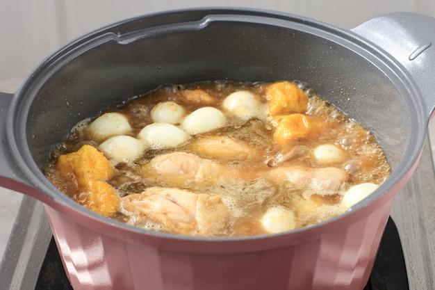 厳選されたフォーカスクッキングオポールアヤム(インドネシアチキンカレー)と豆腐とウズラの卵、キッチンでの調理プロセス。ゆで調理