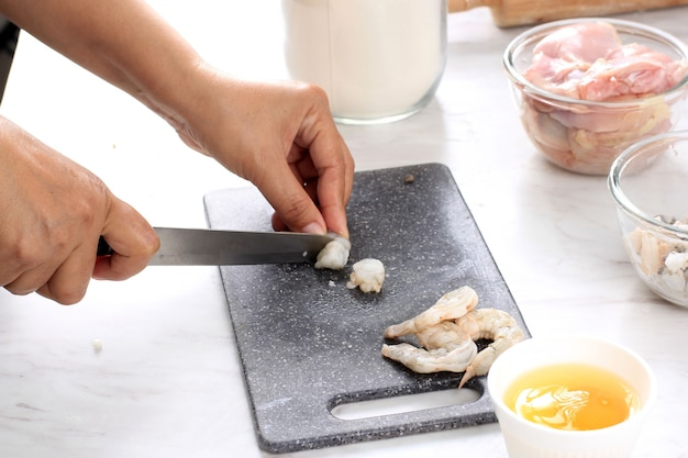 Приготовление к выбранному фокусу: женщина-повар нарезала креветки / креветки с ножом на черной разделочной доске на кухне. пошаговое приготовление пельменей / димсам с курицей и креветками