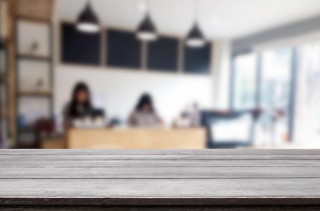 Выбранный фокус пустой коричневый деревянный стол и кофе размытия фон с изображением боке. для вашего фотомонтажа или отображения продукта