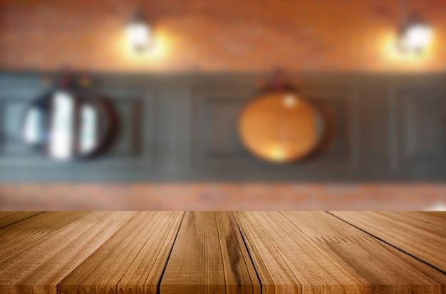 Выбранный фокус пустой коричневый деревянный стол и фон кофе или ресторан размытия с изображением боке. для вашего фотомонтажа или отображения продукта.