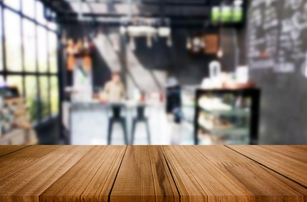 Selected focus empty brown wooden table and coffee shop or restaurant blur background