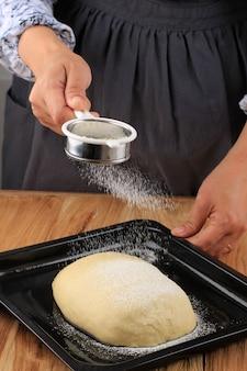 Пекари-женщины в избранном фокусе держат ситечко, покрывая сырое хлебное тесто с мукой