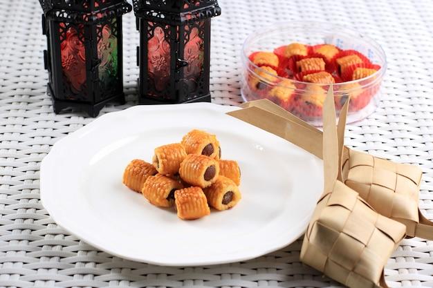 Selected focus fresh baked pineapple tart roll cookies (tart nanas or kuih nenas or nastar gulung). concept of kue lebaran on white background