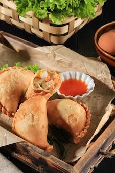 선택한 포커스 프라이드 파스텔 또는 파스텔 고렝은 인도네시아에서 인기 있는 페이스트리의 일종으로, 반죽 위에 당근을 놓고 접고 단단히 닫습니다.