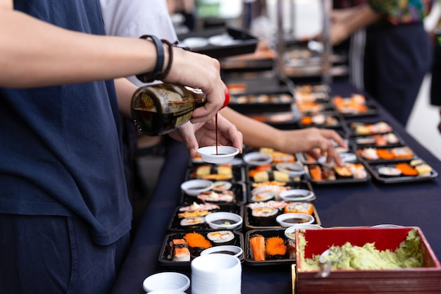Selected focus hand pouring sushi sauce with wasabi on thailand street food japanese sushi